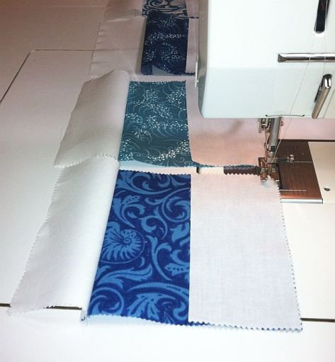 Sew white rectangles to either side of charm square.