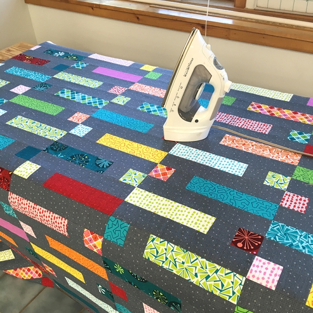 Iron the basted quilt to set the glue